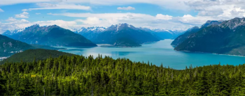 The Alaskan wilderness including hills and mountains, a body of water, and lush forests